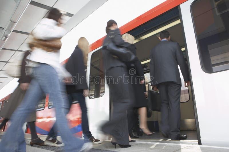 Регулярные пассажиры пригородных поездов дела получая в поезд стоковая фотография rf