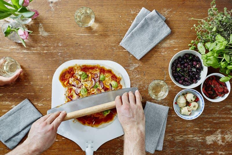 Резать органическую пиццу с ножом пиццы стоковые изображения