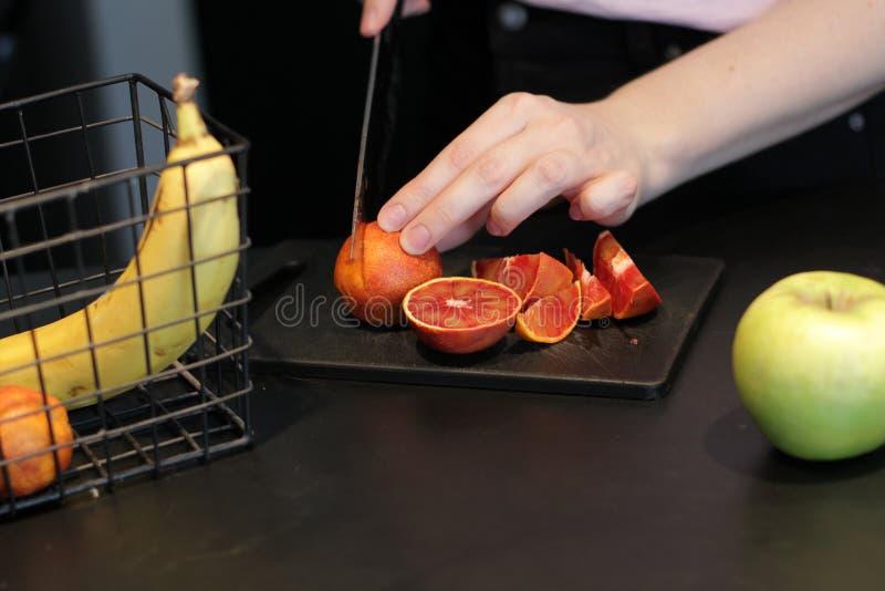 Резать различные плоды с ножом Действие рук Красный апельсин, бананы, яблоки r стоковая фотография rf