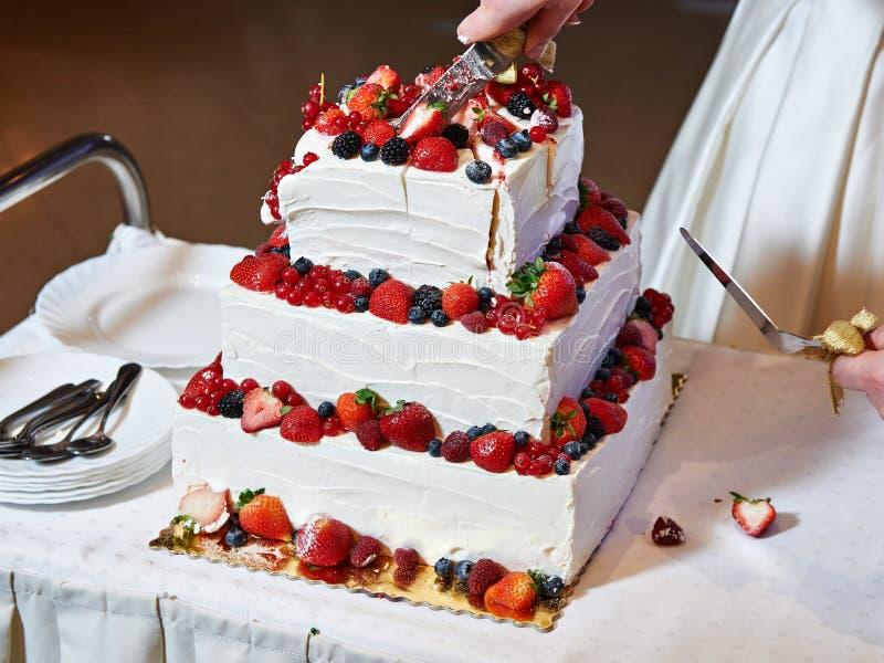 Резать свадебный пирог с ягодами стоковая фотография rf
