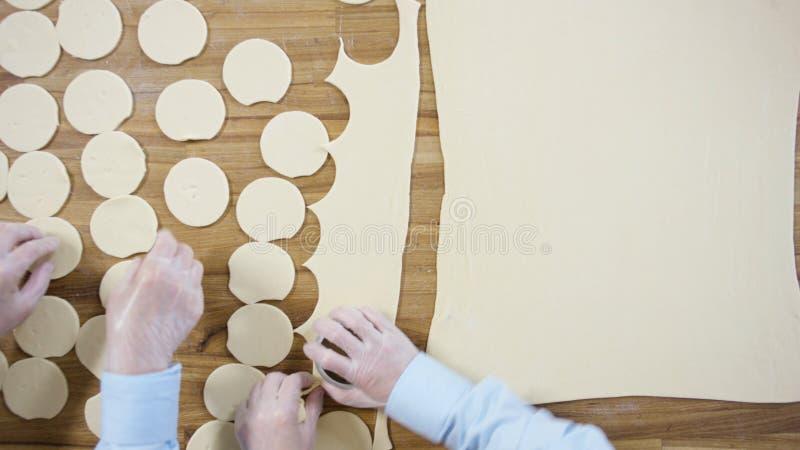 Резать тесто в круги, взгляд сверху место Вареники мяса подготовки Разворачивание тесто и отрезать круги из его стоковые изображения rf