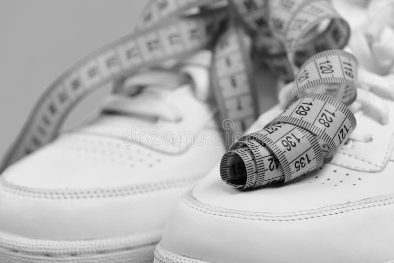 Резвитесь ботинки и sportive оборудование для здоровой формы Сантиметр в cyan голубом цвете завил на белых тренерах стоковые изображения rf