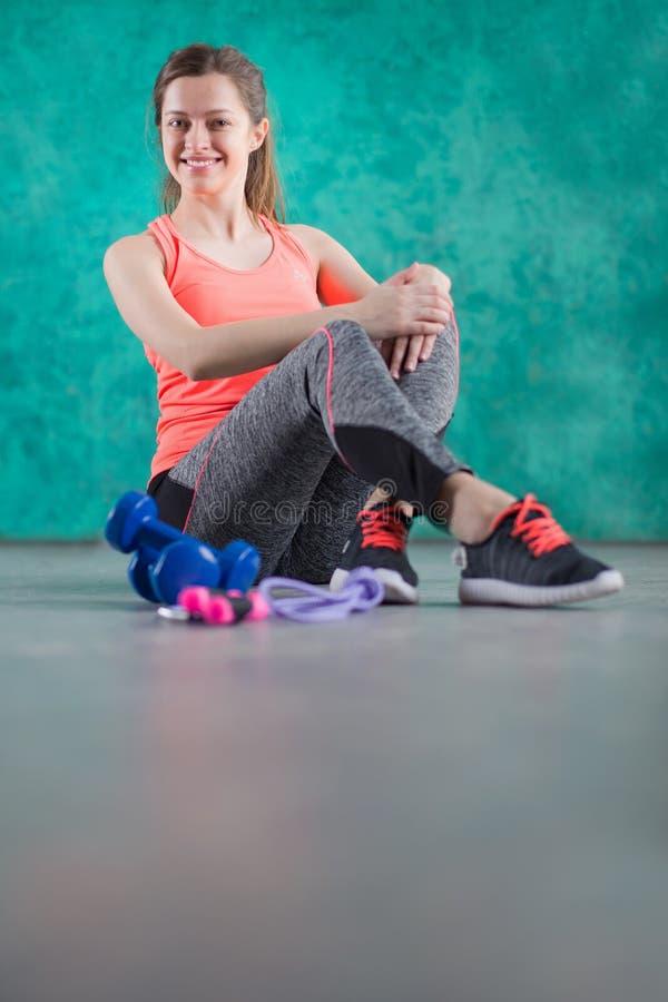 Резвитесь девушка фитнеса с гантелями - на предпосылке бирюзы Помадки нездоровы Высококалорийная вредная пища Dieting, здоровое E стоковое фото rf