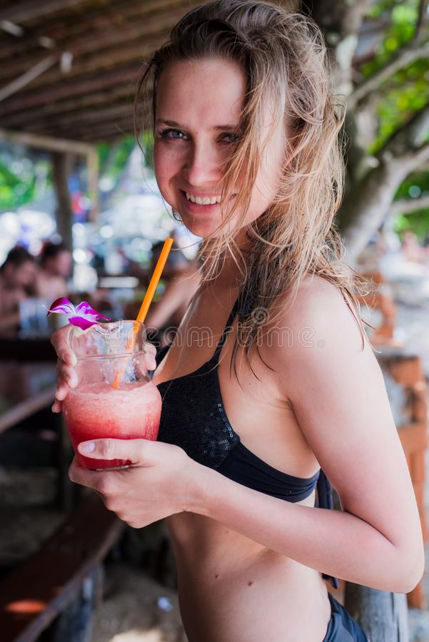 Резвитесь женщина фитнеса выпивая здоровый розовый сок вытрезвителя, vegetable smoothie на лете пляжа outdoors Фитнес здоровый стоковая фотография