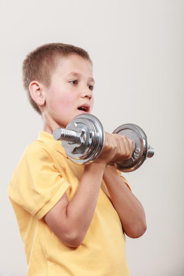 Резвит мальчик делая тренировку с гантелью стоковое фото rf