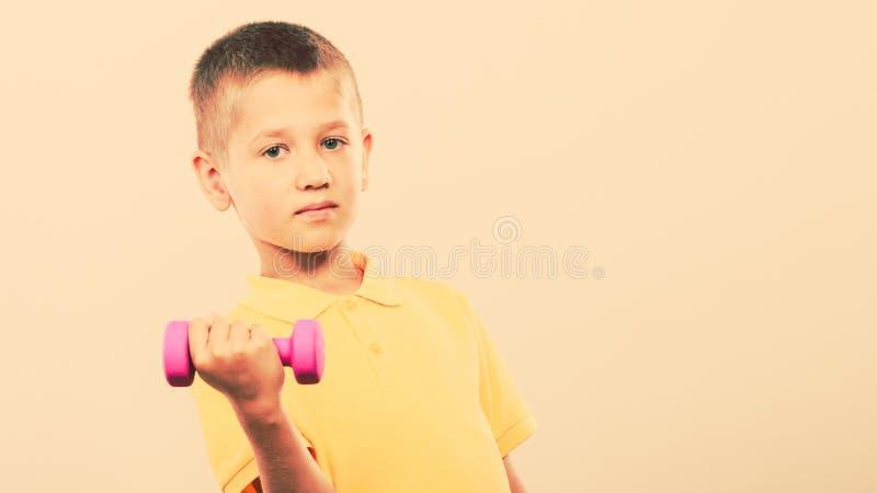 Резвит мальчик делая тренировку с гантелью стоковое фото