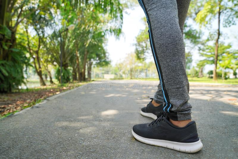 Резвит предпосылка, ноги бегуна бежать на крупном плане дороги на ботинке, женщине спорта бежать на дороге на восходе солнца, фит стоковая фотография rf
