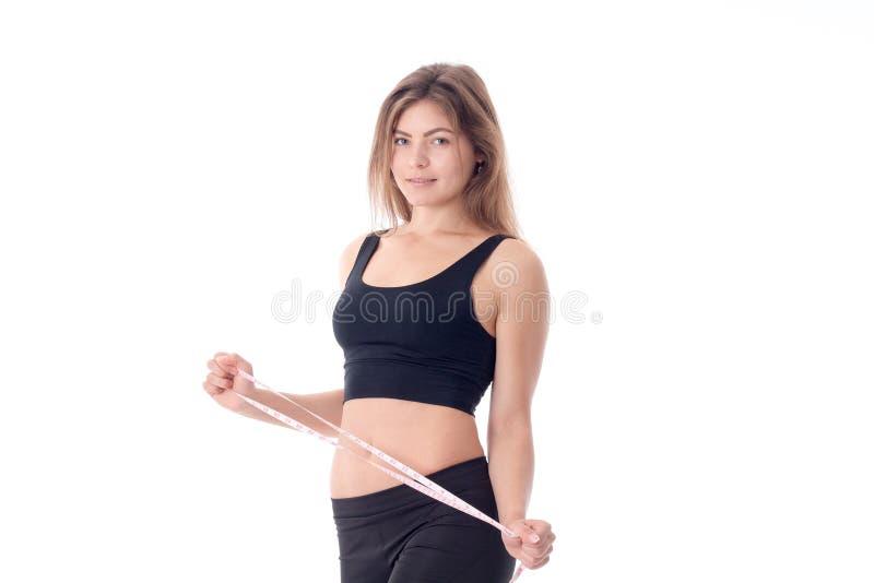 Резвит худенькая девушка в черных колготках и верхней стороне которая держит рулетку стоковые изображения