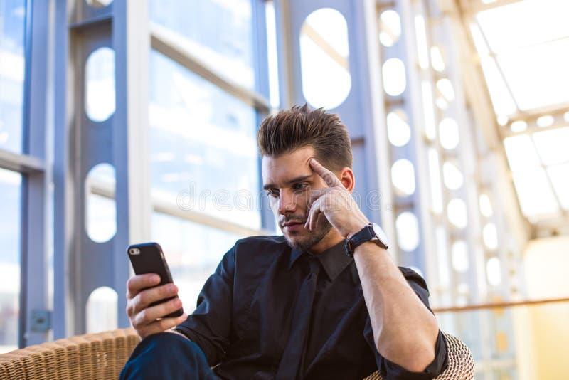 Резервирование уверенного бизнесмена онлайн через мобильный телефон, сидя в зале предприятия стоковые фото
