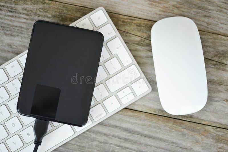 Резервные данные с внешним жестким диском на белой клавиатуре компьютера стоковые изображения