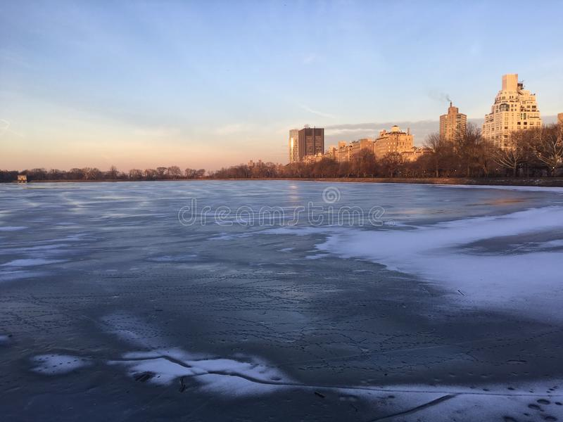 Резервуар Жаклина Кеннеди Onassis с замороженной водой во время захода солнца в зиме в Central Park в Манхаттане, Нью-Йорке, NY стоковая фотография rf