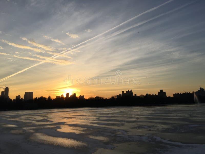 Резервуар Жаклина Кеннеди Onassis с замороженной водой во время захода солнца в зиме в Central Park в Манхаттане, Нью-Йорке, NY стоковое изображение