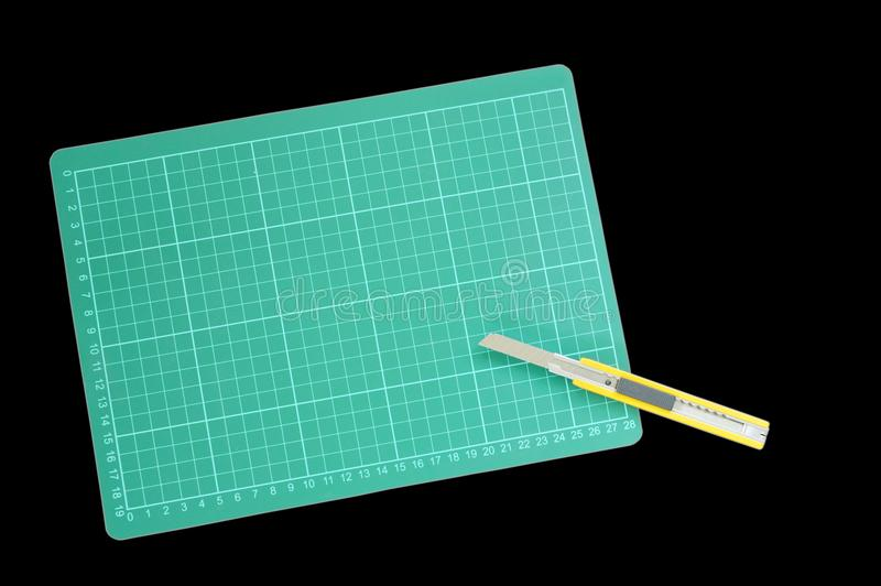 Резец раскрыл лезвие и зеленую разделочную доску на черной предпосылке стоковое фото