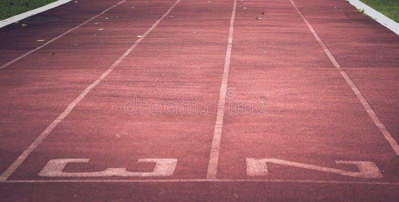 Резина красного идущего следа синтетическая на атлетическом стадионе стоковые фото