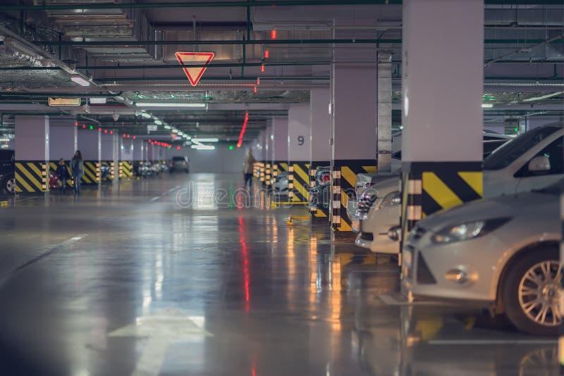 Резюмируйте запачканную автостоянку автомобиля, гараж, интерьер подземной автостоянки с автомобилями в здании торгового центра de стоковое фото rf