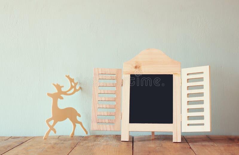 Резюмируйте фильтрованное фото декоративной рамки доски и деревянные оленей над деревянным столом подготавливайте для текста или  стоковая фотография rf
