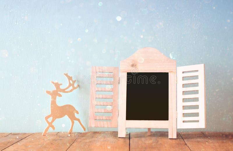 Резюмируйте фильтрованное фото декоративной рамки доски и деревянные оленей над деревянным столом подготавливайте для текста или  стоковые изображения rf