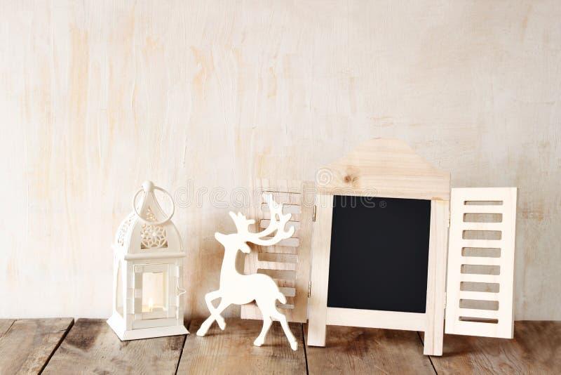 Резюмируйте фильтрованное фото декоративной рамки доски и деревянные оленей над деревянным столом подготавливайте для текста или  стоковые фото