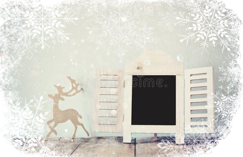 Резюмируйте фильтрованное фото декоративной рамки доски и деревянные оленей над деревянным столом подготавливайте для текста или  стоковое фото