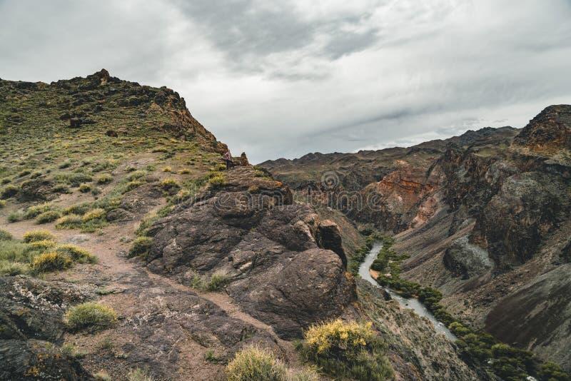 Река в каньоне Charyn в Казахстане с горами и небом заволакивает стоковое изображение