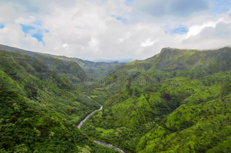 Река извиваясь через зеленый ландшафт, побережье Na Pali, Кауаи, Гаваи стоковая фотография rf