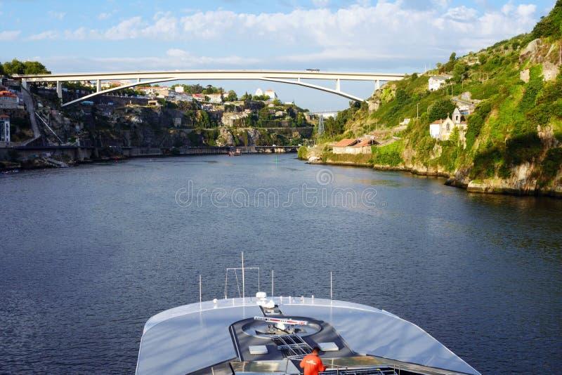 Река, мост, крыши домов и большая белая шлюпка круиза удовольствия в свете заходящего солнца стоковая фотография