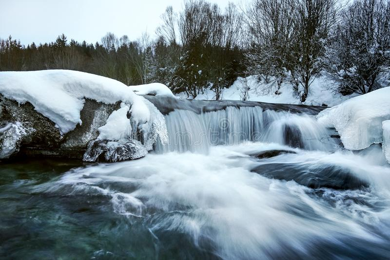 Река покрытое со снегом и льдом в зиме, предпосылке деревьев, фото долгой выдержки с milky ровной подачей воды стоковая фотография rf