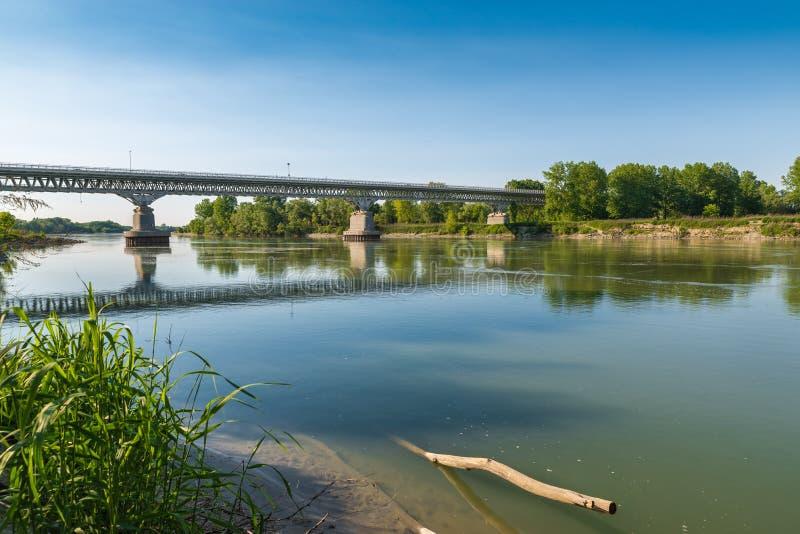 Река По на средневековом городке пьяченцы, Италии Мост автомобиля то водит к городу Река По самое длинное итальянское река стоковая фотография rf