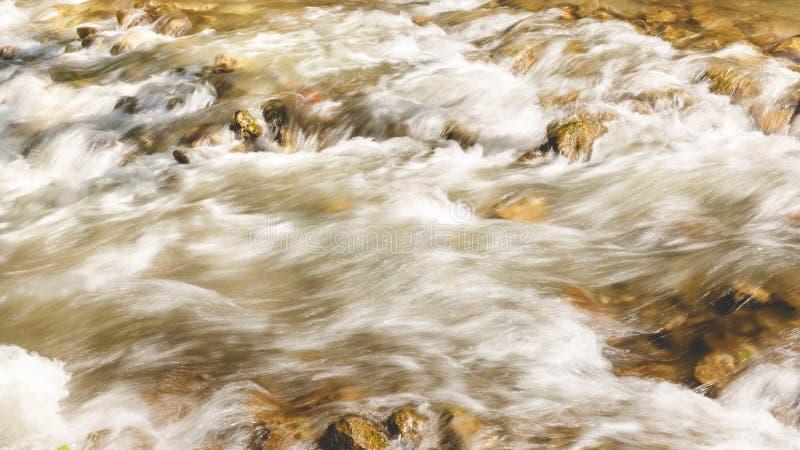 Река пропуская через утесы, конец вверх стоковые изображения