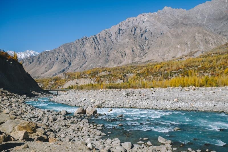 Река сини бирюзы пропуская через долину Hunza Nagar в сезоне осени с целью горной цепи Karakoram стоковые изображения