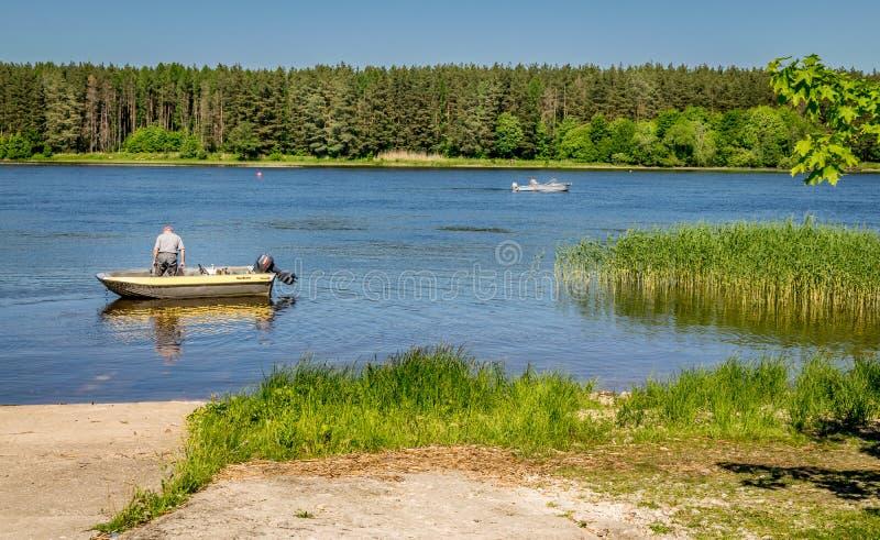 Река с лесом, тростниками и рыболовы в 2 шлюпках стоковое фото