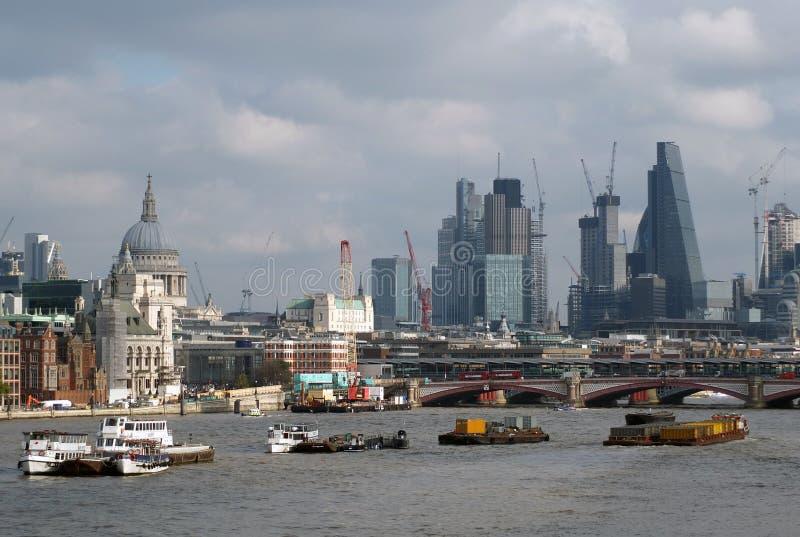 Река barges на thames в позднем вечере с городом зданий Лондона современных финансовых и историческом разбивочном видимом в стоковое фото rf