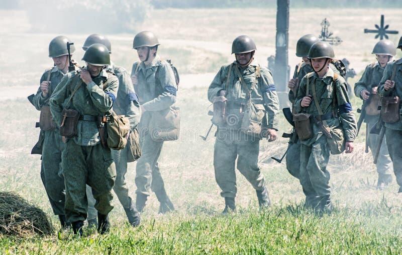 Реконструкция Второй Мировой Войны, группа в составе утомленный немец так стоковое фото rf