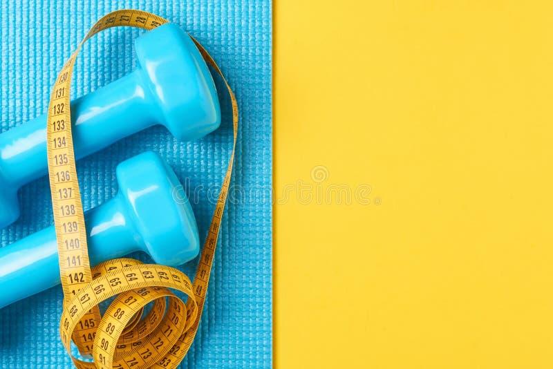 релаксация pilates пригодности принципиальной схемы шарика Гантели и измеряя лента на голубой и желтой предпосылке, положении взг стоковое фото rf