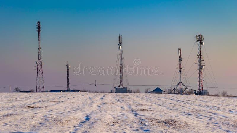реле телекоммуникаций на снежном поле увиденном в зиме стоковое фото rf