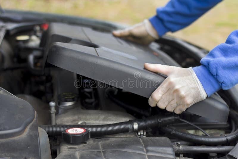 Ремонтная мастерская автомобиля Механик положил дальше пластичный чехол двигателя стоковые фото