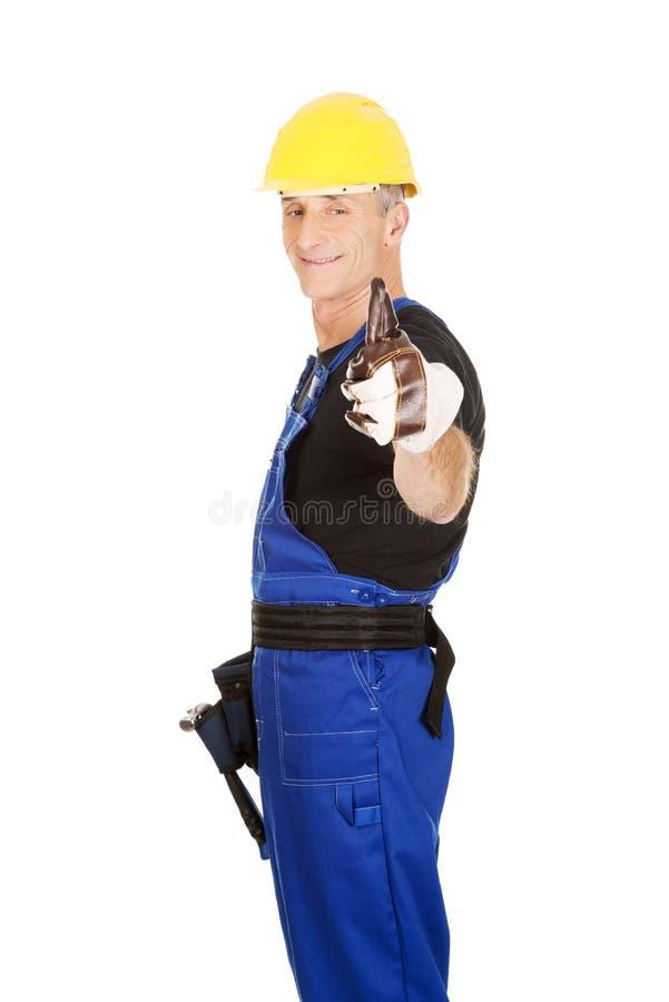 Ремонтник взгляда со стороны показывая большие пальцы руки вверх стоковая фотография