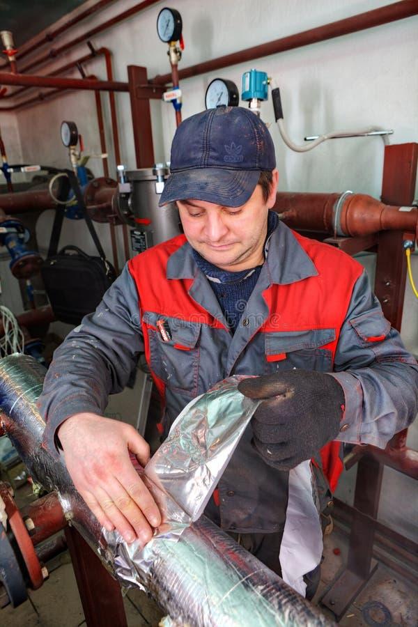 Ремонтник инженера трубопровода работая в котельной, изолирует стоковая фотография