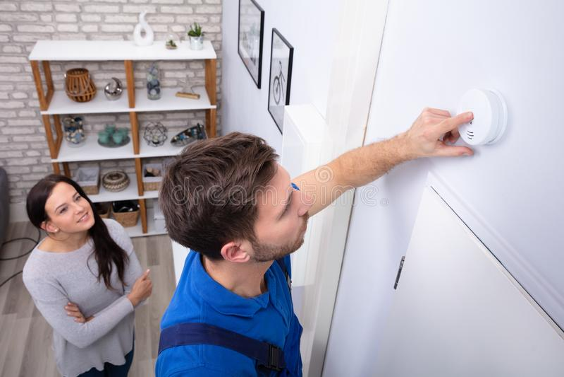 Ремонтник устанавливая индикатор дыма на стену стоковые изображения rf