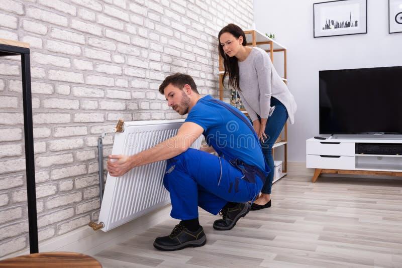 Ремонтник устанавливая радиатор на кирпичную стену дома стоковое изображение