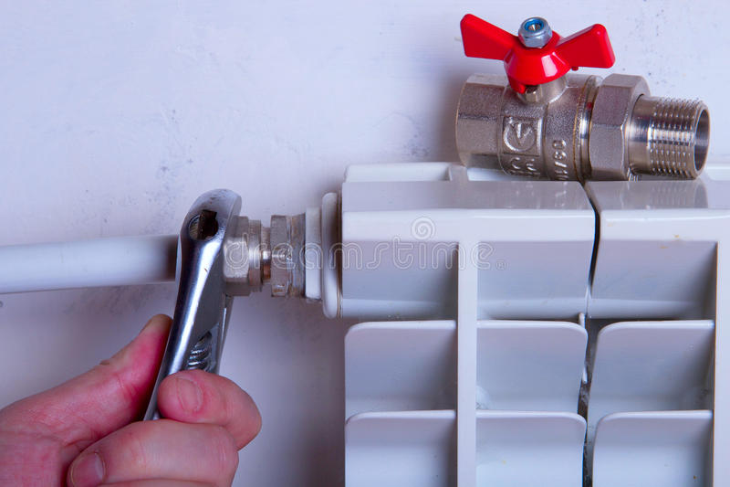 Ремонты радиатора водопроводчика используя ручные резцы стоковое фото rf