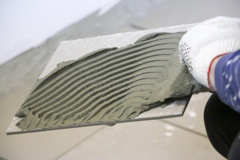 Ремонт - внутреннее художественное оформление Класть плиток пола керамических Tiler рук ` s людей в перчатках с шпателем распрост стоковое фото