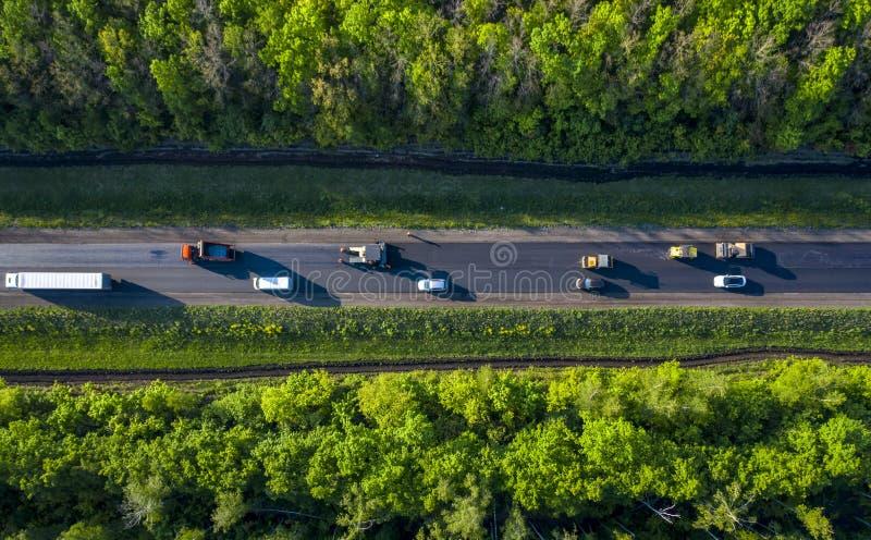 Ремонт дороги, кладя горячий асфальт на дорогу идя через лес, взгляд от трутня quadcopter стоковое фото rf