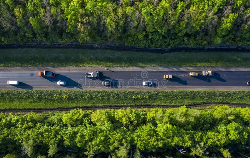 Ремонт дороги, кладя горячий асфальт на дорогу идя через лес, взгляд от трутня quadcopter стоковые фотографии rf