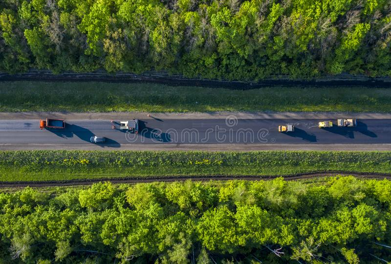Ремонт дороги, кладя горячий асфальт на дорогу идя через лес, взгляд от трутня quadcopter стоковые фото
