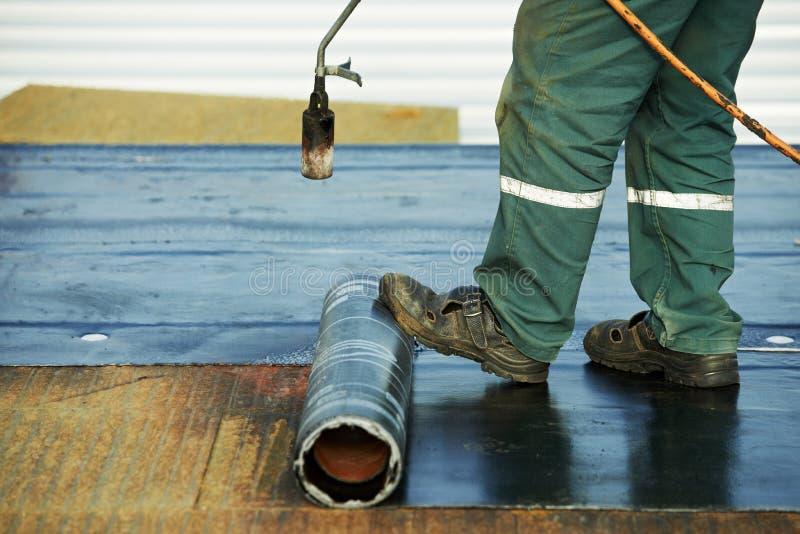 Ремонт заволакивания плоской крыши работает с войлоком толя стоковое фото rf