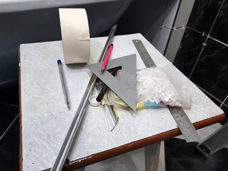 Ремонт - здание с инструментами, рулетка, карандаш, ручка, отметка, лента для маскировки, треугольник, угол, углы плитки, алюмини стоковые изображения rf