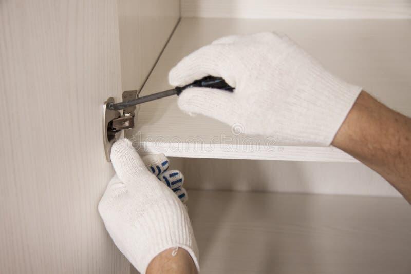 Ремонт и установка мебели в комнате Мужские руки ` s работника в белых перчатках стоковые фотографии rf