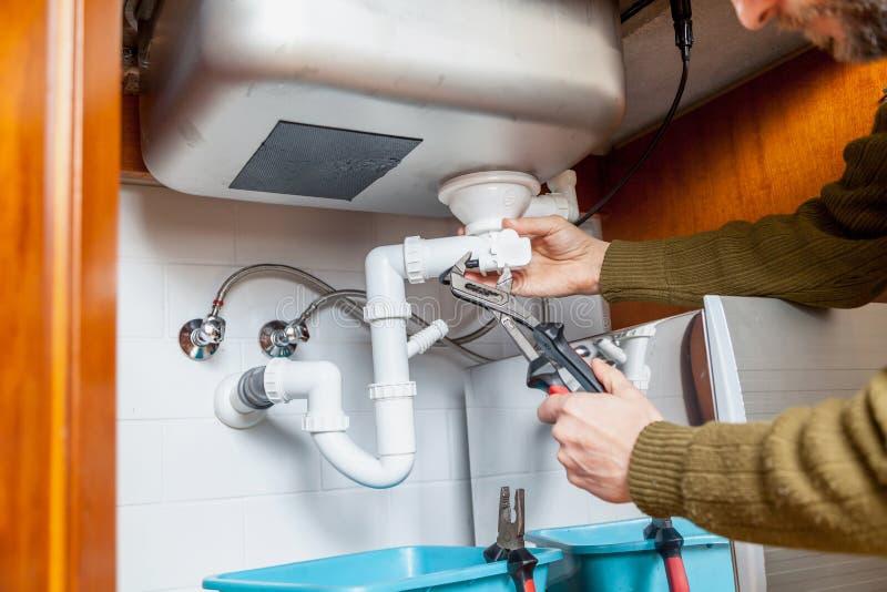 Ремонт крупного плана ключа для труб переполнения кухни стоковое фото