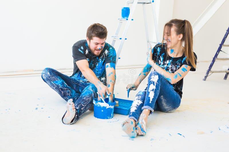 Ремонт, реновация и концепция людей - пара идя покрасить стену и иметь потеху на перерыве стоковые фотографии rf